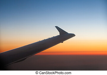 Wing of a Airplane at sunset with clouds