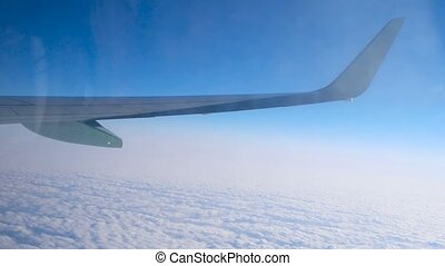 Wing of aircraft flying over cloud cover