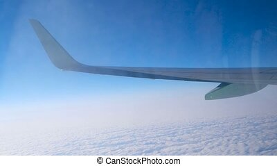 Wing of aircraft flying over cloud cover, view through dirty window with reflections