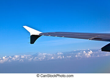 wing of aircraft in blue sky