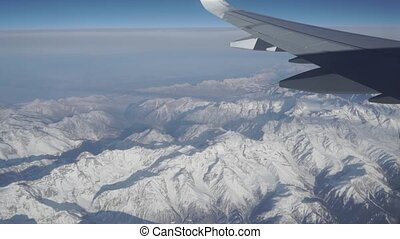 Wing of airliner against distant snow covered mountains