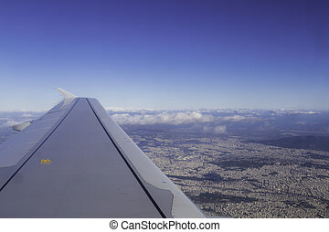 Wing of airplane above cityscape, view from window.