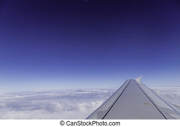 Wing of airplane above the clouds in the sky, view from window.
