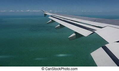 Wing of airplane flying above sea