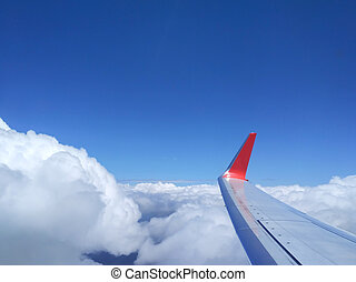 Wing of airplane flying above the clouds from window