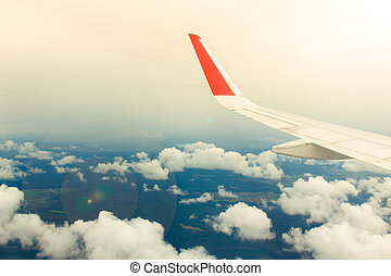 Wing of airplane from window on the background of blue sky