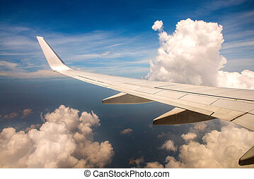 Wing of airplane in cloudy sky