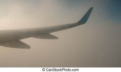 Wing of airplane in rolling clouds, view from window