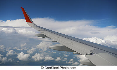 Wing of airplane on sky and cloud on moving