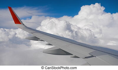 Wing of airplane on sky and cloud on moving, view from...