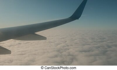 Wing of airplane over the clouds, view from window.