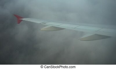 Wing of flying airplane in a fog