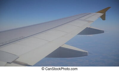 Wing of passenger airplane, the view through the window