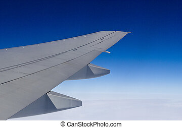 Wing of the plane and the dark blue sky
