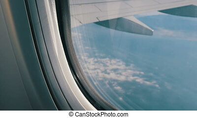 Wing of the plane flies over beautiful clouds. View from the window