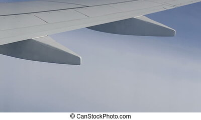 Wing of the plane flies over the clouds