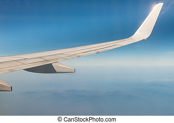Wing of the plane on blue sky background and mountains below