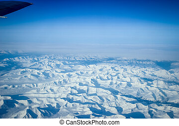 Wing of the plane on blue sky background and snowy mountains, view from window