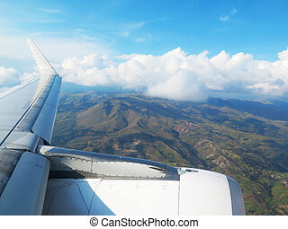 Wing of the plane on blue sky, clouds and mountains