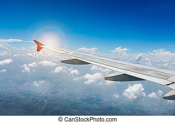 Wing of the plane on blue sky with sunlight. travel concept