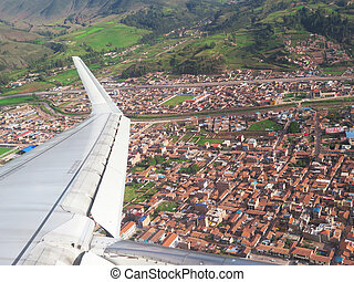 Wing of the plane on Cuzco city and mountain