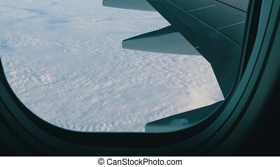 Wing of the plane through the porthole. The plane flies over...