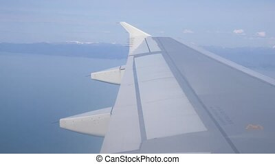 Wing of Wing of plane. A view of the sea and mountains from the plane during take-off or landing. 4k