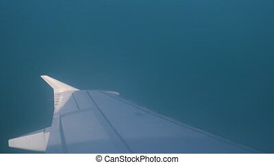 Wing of Wing of plane. A view of the sea and mountains from the plane during take-off or landing.