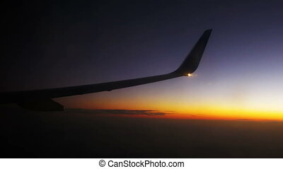 Wing Plane Flying in the Sky Against a Background of Sunset