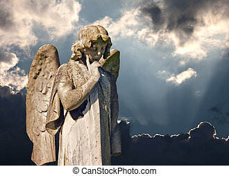Winged angel statue in ancient graveyard