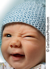 Winking Baby Blue Hat - Close up of happy baby winking and ...