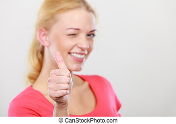 Winking blonde woman showing thumb up