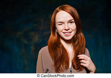 winking red-haired woman posing