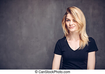 Winking young caucasian woman on dark background