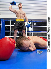 Winner and loser. Confident young boxer keeping his arm raised while his opponent lying down on the boxing ring