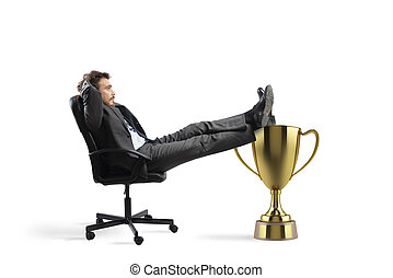 Winner businessman relaxing over a golden cup