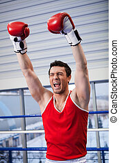 Winner. Cheerful young boxer keeping his arms raised while...