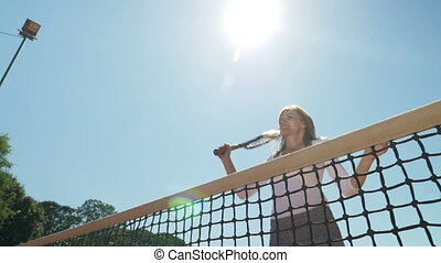 Winner girl jumping at the net and laughing happily...