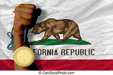 Winner holding gold medal for sport and flag of us state of california