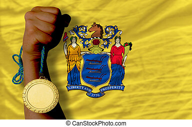 Winner holding gold medal for sport and flag of us state of new jersey