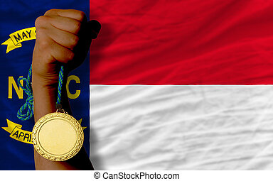Winner holding gold medal for sport and flag of us state of north carolina