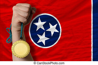 Winner holding gold medal for sport and flag of us state of tennessee