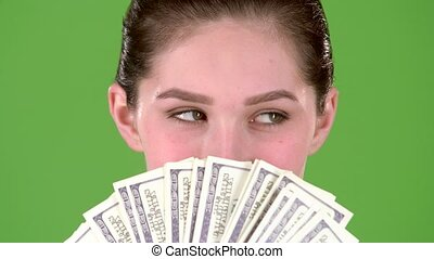 Winner holds a lot of money in her hands. Green screen. Close up