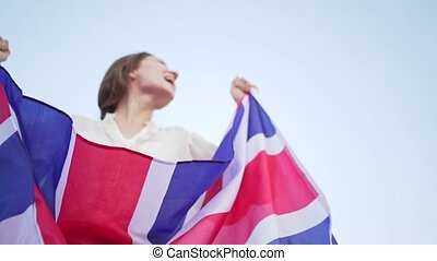 Winner in the UK. Woman with British flag rejoices in success and shouts at the camera.
