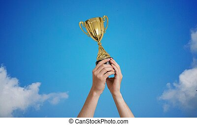 Winner is holding a trophy in hands against blue sky.
