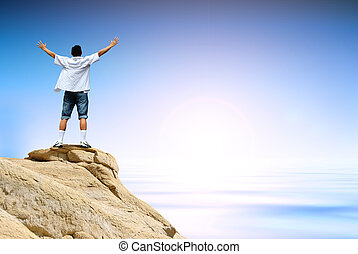 Winner man on mountain top - Man with arms raised in the...