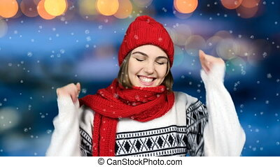 Winner, success concept. 4K video of happy overjoyed winter woman jumping into frame celebrating success gesturing thumbs up, colorful bokeh background
