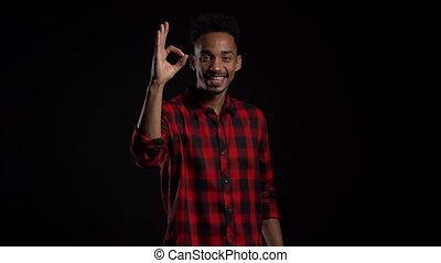 winner., success., heureux, américain, africaine, signe., type, donne, geste, beau, projection, usure, studio, approval., sourires, rouges, appareil photo, arrière-plan noir, homme, ok