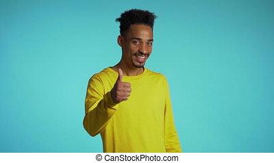 winner., success., heureux, jaune, type, donne, geste, projection, usure, studio, approval., jeune, sourires, haut., appareil photo, arrière-plan bleu, homme, pouces