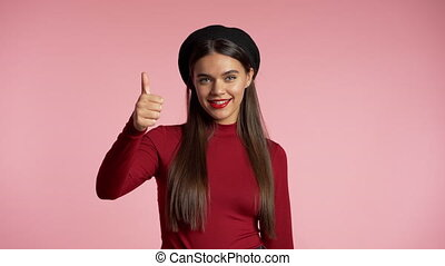 Winner. Success. Positive girl making thumbs up sign over pink background and smiles to camera. Body language. Young hipster woman with perfect red lips make-up and french hat.